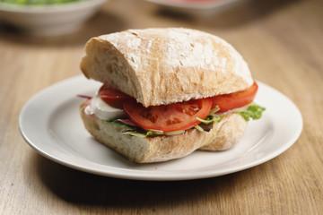 ciabatta sandwich with speck, mozzarella and vegetables