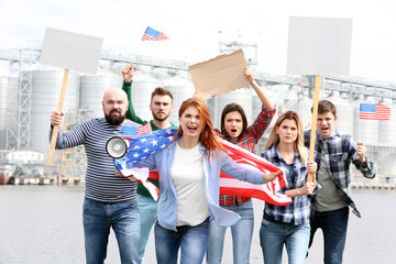Group of protesting young people with American flag and factory on background