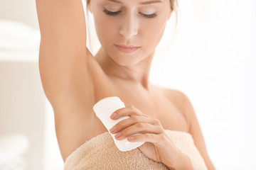 Beautiful young woman with deodorant at home