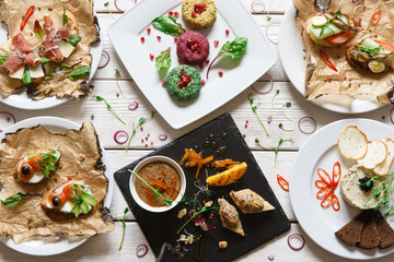 Dinner table with different appetizers. Snacks, paste and small canapes with spices decoration on wooden white background