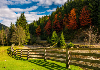 wooden fence near forest river in autumn mountains