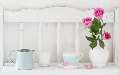 pinc roses in vase and dinnerware on white wooden shelf