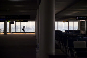 The silhouette view of a young businessman is walking in terminal with panoramic windows.
