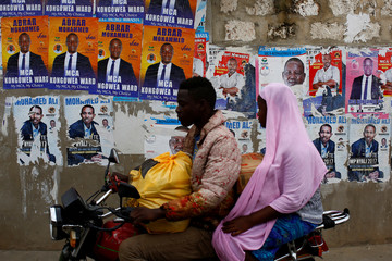 A woman sits on the back of a motorbike taxi as she passes by a wall pasted with campaign posters ahead of the presidential election in Mombasa