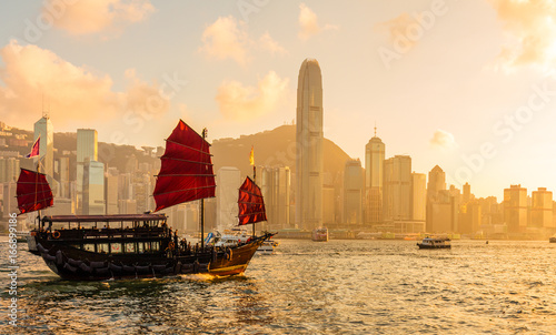 Wall mural Chinese wooden red sails ship in Hong Kong Victoria harbor at sunset time