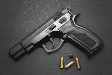 Handgun with ammunition on dark background