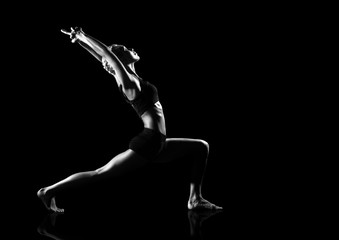 low key black and white studio picture of a yoga warrior pose isolated on black