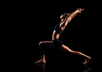 low key studio picture of a yoga warrior pose isolated on black