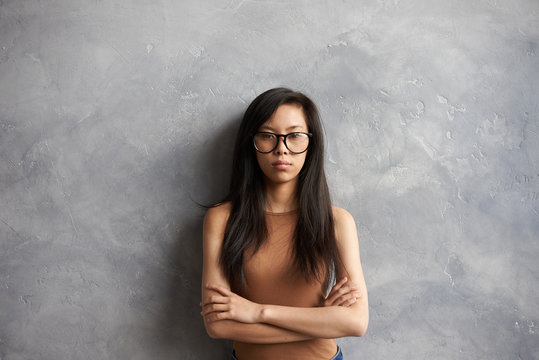 Isolated waist up portrait of serious young brunette woman of Asian appearance wearing glasses posing at blank wall with arms crossed, feeling unhappy or angry after fight with her boyfriend