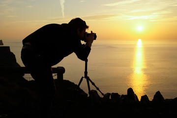 male travel landscape photographer taking pictures of the view sunset with camera
