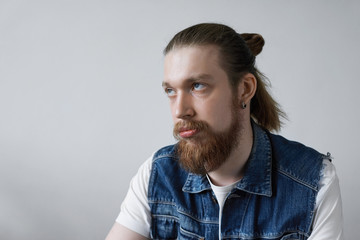Headshot of fed-up young European hipster man with facial hair and bun rolling his eyes while feeling annoyed or irritated with something, having displeased and bored look. Human emotions and feelings