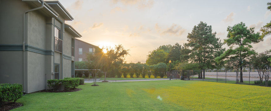 View from grassy backyard of a typical apartment complex building in suburban area at Humble, Texas, US. Dramatic sunset cloud with warm light, iron fence and row of pine trees. Panorama