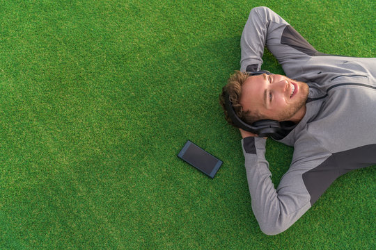 Happy man listening to music with headphones and phone relaxing on green grass lying down with arms behind head enjoying summer day in park. Young adult using mindfulness smartphone app concept.