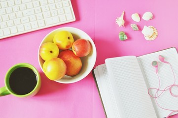 Feminine work space flat lay/ White computer keyboard, peaches, coffee cup, open notebook, headphones and seashells on a pink background