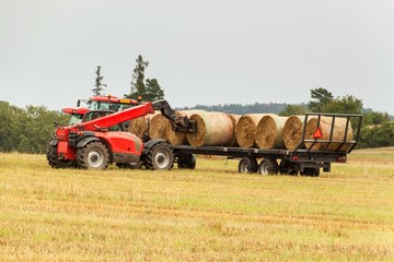 Telescopic collector straw collector on field in the Czech Republic. Work on an agricultural farm. Collecting straw bales.