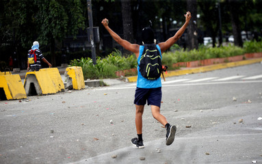A demonstrator holds rocks during clashes with security forces near Fuerte Paramacay military base in Valencia