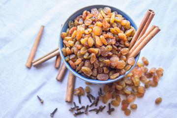 A raisin in the blue bowl . Cinnamon sticks.