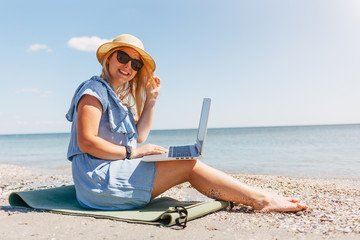 Young beautiful woman sitting with laptop on the beach near the sea
