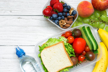 School lunch boxes with sandwich, fruits, vegetables and bottle of water and copy space