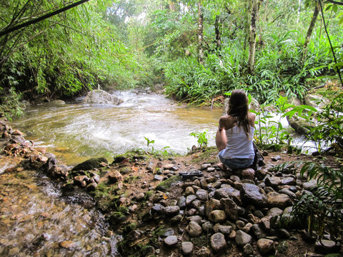 Young woman sitting by the river in a tropical forest