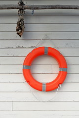 Red lifesaver and codfish head hanging on the white wall. Hamnoy-Reine-Moskenes-Lofoten-Norway. 0240
