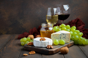 Variety of cheese with grapes, walnuts and wine. Selective focus, copy space.