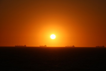 Container ships in front of Fremantle, sunset in Indian Ocean view from Cottesloe Beach, Western Australia