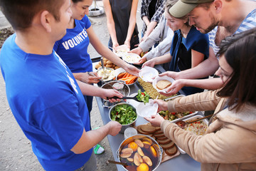 Volunteers sharing food with poor people outdoors. Poverty concept