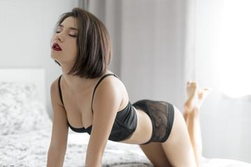 Erotic woman in erotic lingerie posing on bed