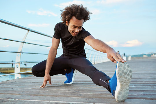 Dark-skinned man athlete in black sportswear and blue sneakers stretching his legs with lunge hamstring stretch exercise on the pier. Afro-American young male runner warming-up his muscles before