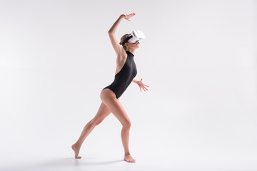 Somber youthful woman simulating dance from goggles