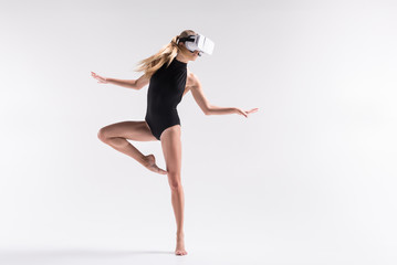 Thoughtful youthful sporty woman performing choreography using goggles
