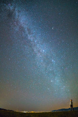 The man stand against the background of the milky way. night time
