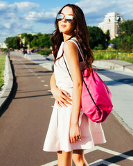 Summer portrait of an asian girl in a summer bright outfit and sunglasses with a pink backpack on the road. Los Angeles, California.
