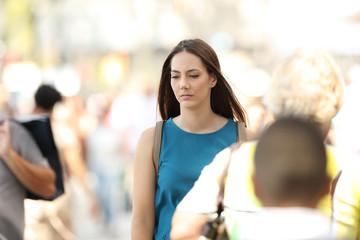 Woman feeling alone walking between people