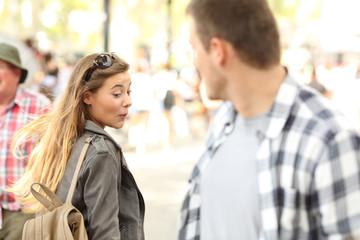 Sassy girl looking at man bottom on the street