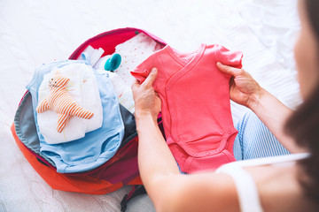 Pregnant woman packing suitcase, bag for maternity hospital