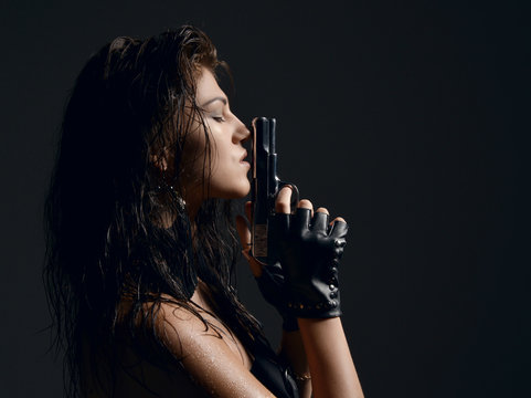 Closeup portrait of beautiful sexy brunette woman with old revolver gun