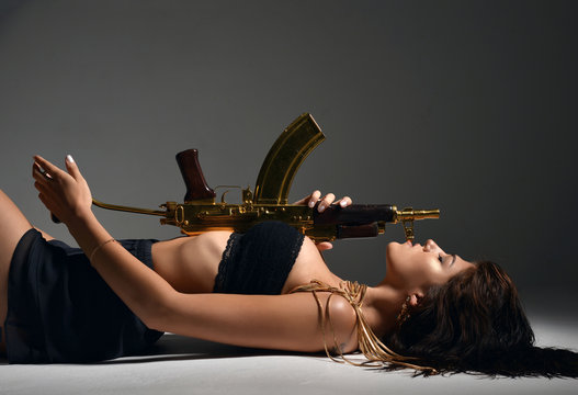 sexy brunette woman lying with fashion gold automatic rifle gun on gray background