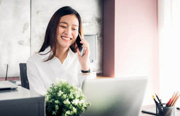 Asian businesswoman talking on mobile phone in front of laptop computer at office,Office lifestyle concept