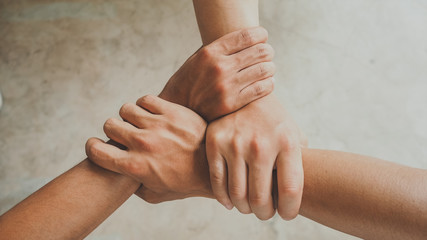 Three human join hands together, collaboration concept of business and education teamwork, soft focus and vintage color tone process Wall mural