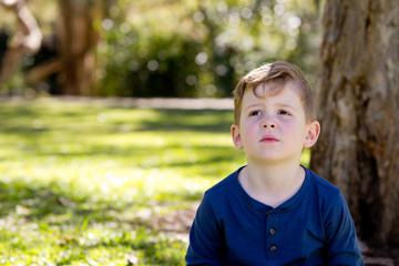 Young boy thinking and looking up - sitting crossed legged against tree trunk in park