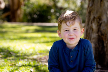 Young boy quietly sitting crossed legged against tree trunk in park - with copy space