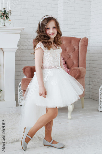 b8ba011973aec Beautiful little girl with curls and white Quinceanera dresses with a train  on the background of the fireplace and chairs