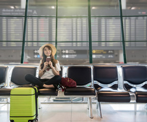 Happy Asian woman traveler holding the passport with suitcases and waiting for airplane arrive in modern an airport with travel information board background, travel and transportation concept.