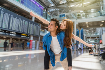 Happiness Asian couple traveler at the flight information screen in moddern an airport, lifestyle travel and transportation concept.