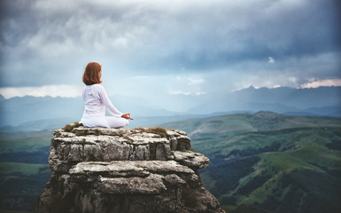 woman practices yoga and meditates in   lotus position on mountains, peak