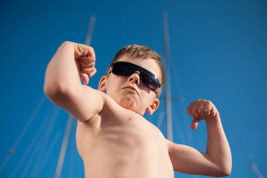 healthy preschool child showing his biceps outdoors summer