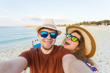 Happy traveling couple in love taking a selfie on phone at the beach on a sunny summer day. Pretty girl and her handsome boyfriend having fun, crazy emotional faces , laughing.