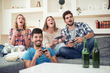 Young friends drink beer and play video games